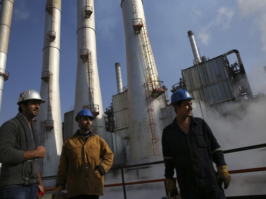Iranian oil workers gather at an oil refinery south of the capital Tehran, Dec. 22, 2014. Iran's oil exports have been crippled by sanctions.