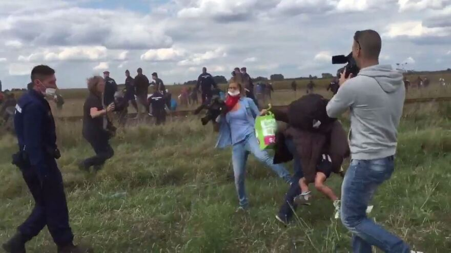 "Camerawoman Petra Laszlo trips a migrant holding a young boy as he tries to run past a police collection point in Hungary. ""I'm not a heartless, racist, children-kicking camerawoman,"" Laszlo later said."
