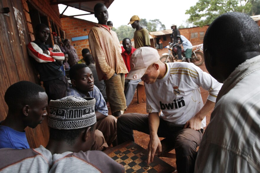 Maajabu Boaz, 20, who has albinism, plays checkers with local men where he feels safe in Nengo Village, Kibondo, Tanzania. Boaz has a reputation of carrying knives for self-protection.