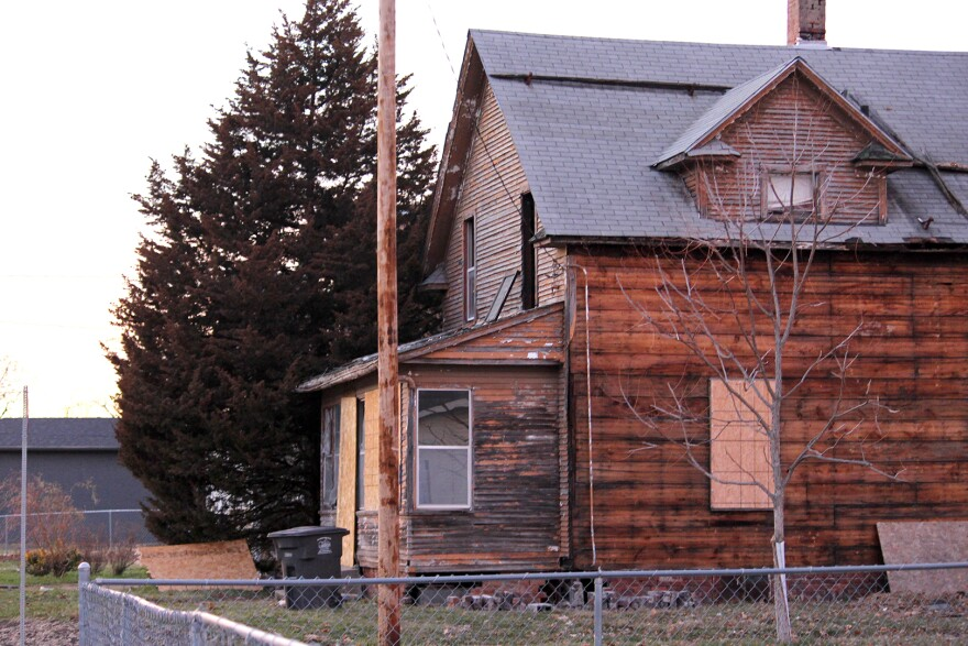 A century-old home sit on a street corner with the siding stripped off and boards over the windows.