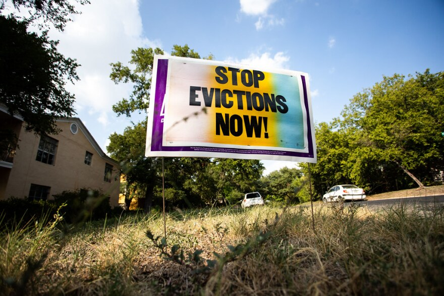 "A sign in Central Austin says ""Stop Evictions Now."""