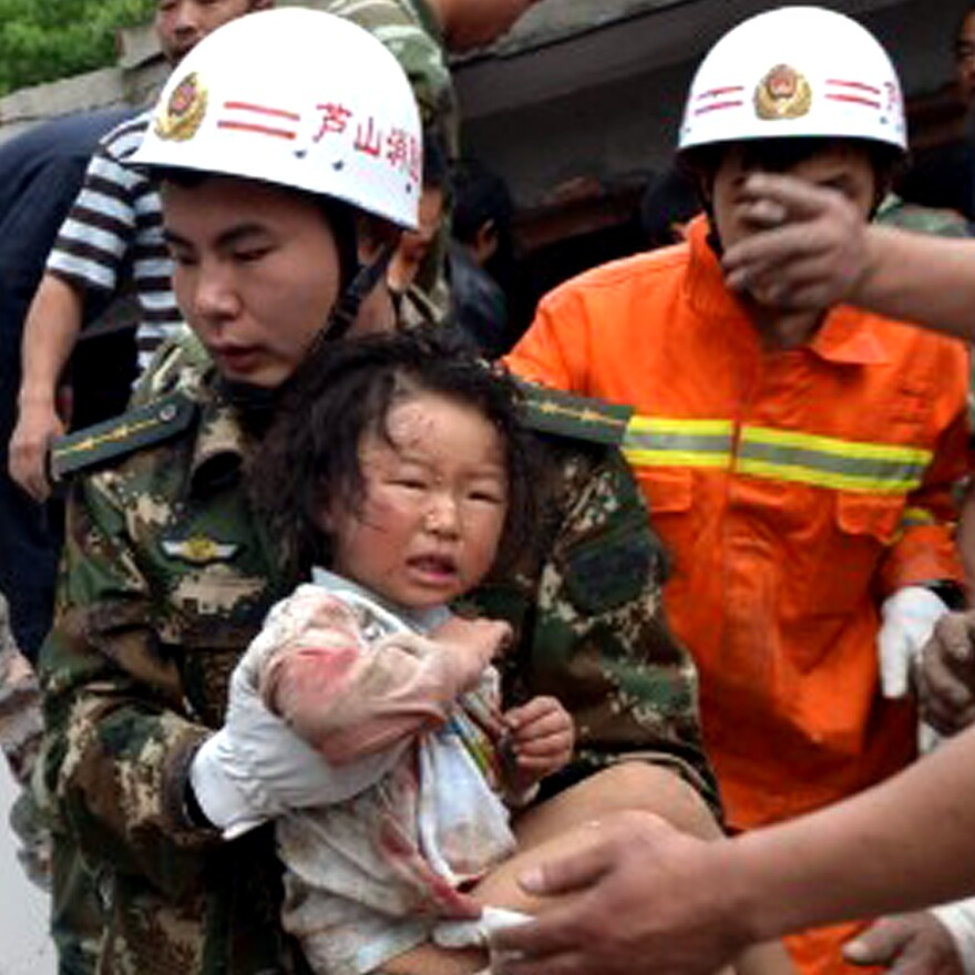 A rescuer carries a child to safety after she was pulled out of her collapsed home after an earthquake hit Ya'an City in southwest China's Sichuan province on Saturday.