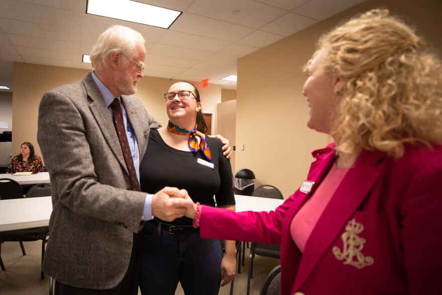 Bastrop County Judge Paul Pape drapes his arm around Clara Engle, while shaking Susan Walch's hand before a meeting on the census.
