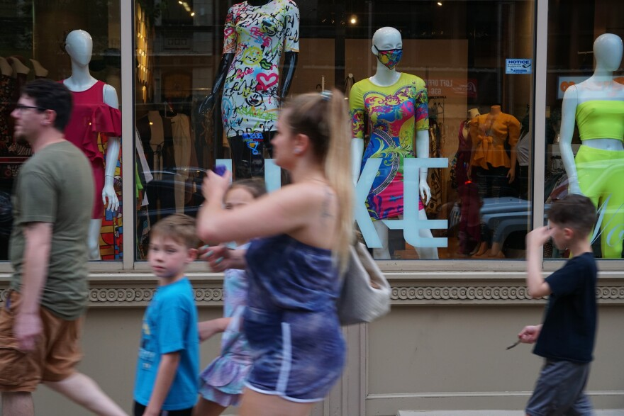 People pass a window display featuring outfits with matching coronavirus masks on Washington Avenue in downtown St. Louis on June 19, 2020.
