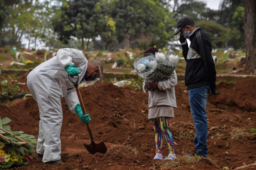 An employee digs next to relatives of a person who died from COVID-19 at the Vila Formosa cemetery, in the outskirts of Sao Paulo, Brazil.