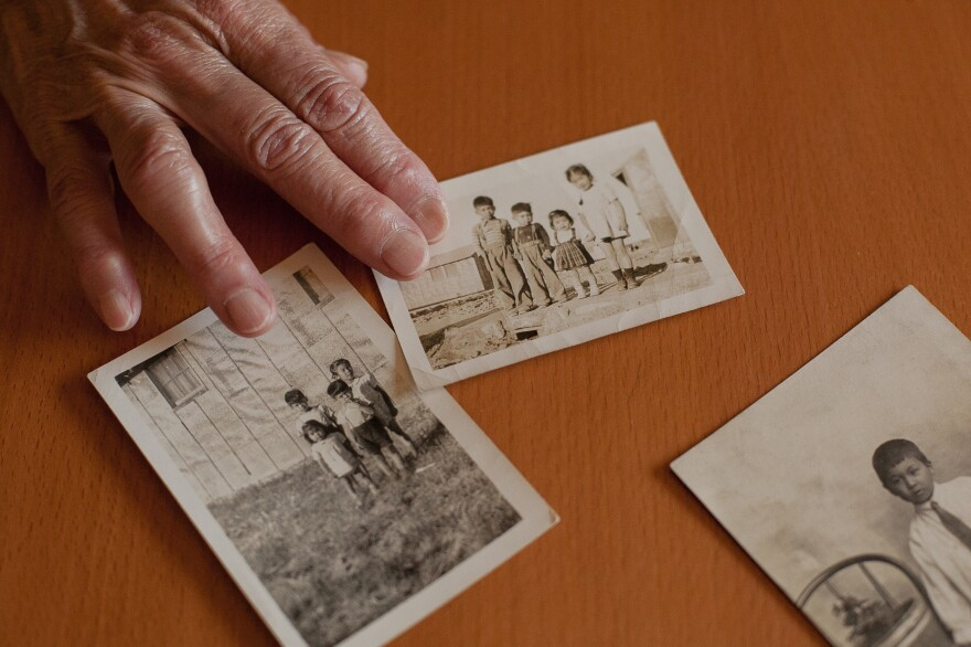 Sharon Sakamoto shows two family photos of Eileen Okada and her other older siblings, who spent part of their childhood living in a barrack behind barbed wire at an Idaho prison camp the U.S. government named the Minidoka War Relocation Center. The third photo is a portrait of their father, Roy Sakamoto, as a young boy.