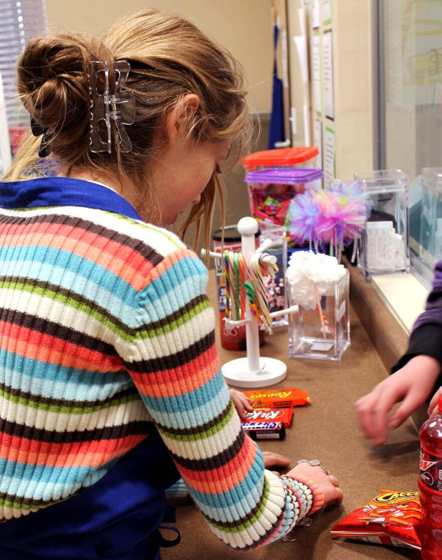 Eighth-grader Kymira Jackson works at Highmark Charter School's store, where students buy little treats with money earned by turning in homework on time and performing chores.