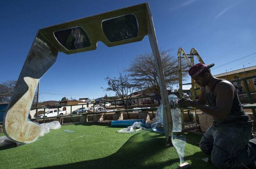 A worker puts finishing touches on a giant pair of eclipse sunglasses at the entrance of La Higuera — about 360 miles north of Santiago, the Chilean capital.