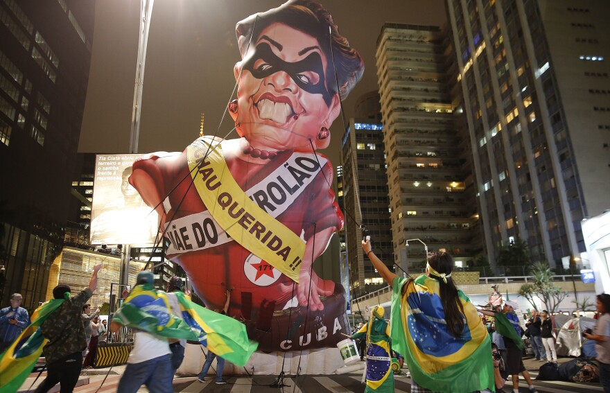 "Protesters parade an inflatable doll of Brazil's President Dilma Rousseff in Sao Paulo on Wednesday night, shortly before Congress voted to suspend her. The sashes say ""Goodbye Dear"" and ""Mother of Big Oil."" Rousseff, the president since 2010, now faces an impeachment trial."
