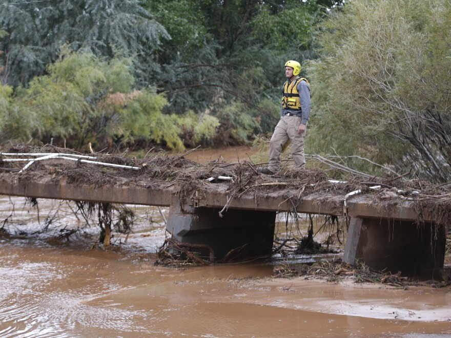 A member of a search and rescue team scans a stream after a flash flood in Colorado City, Ariz. Officials say the bodies of two people killed in flash flooding in southern Utah were recovered in Arizona about two and a half miles downstream.