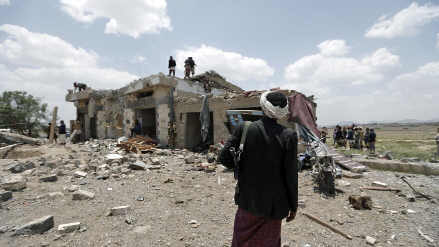 Yemenis stand at the site of an airstrike in the Arhab area, north of Sanaa, on Wednesday.