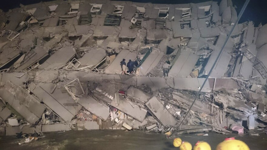 Rescuers are seen entering an office building that collapsed on its side from an early morning earthquake in Tainan, southern Taiwan, Saturday. The quake's magnitude was 6.4, according to the U.S. Geological Survey.