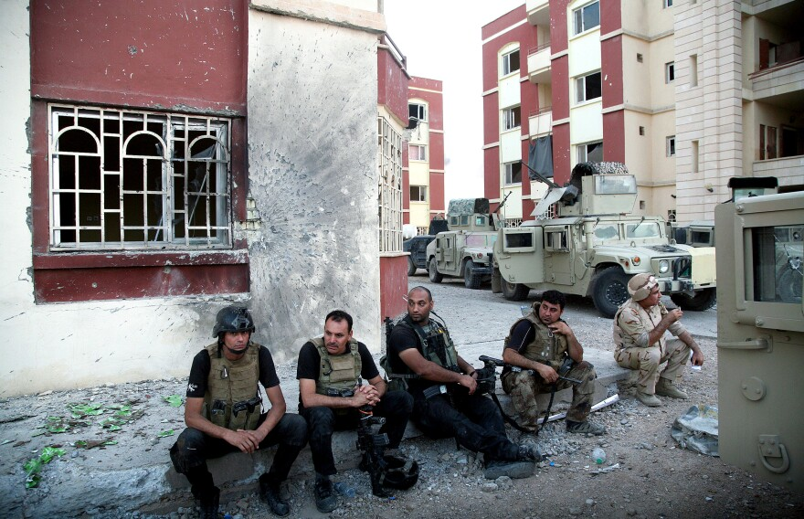 Iraqi security forces rest on a sidewalk following clashes with militants last month in Ramadi, the capital of Anbar province. So far, the Iraqi forces have not been able to recapture cities and towns in western Iraq that the Islamic State seized earlier this year.