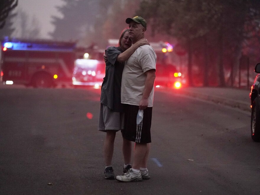 A couple embrace on Thursday while touring an area devastated by the Almeda Fire in Phoenix, Ore.