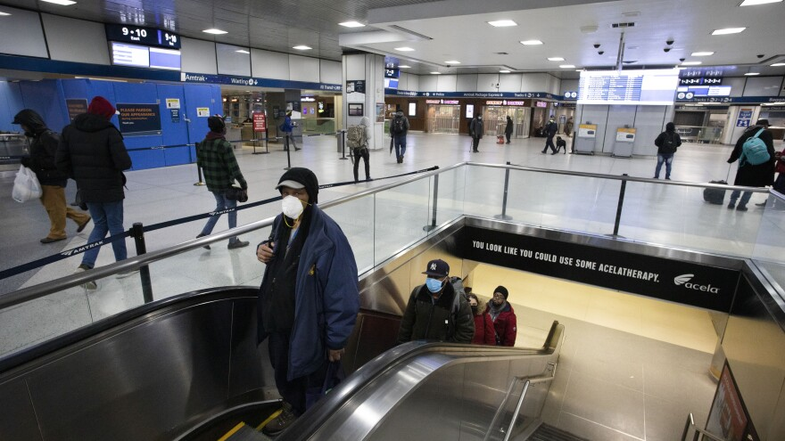 New York Gov. Andrew Cuomo says that in his state — the U.S. epicenter for the coronavirus — the wave of new cases is still going up. Here, commuters wearing masks pass through New York City's Penn Station on Monday.