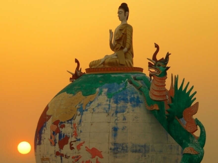 A globe Buddha is visible against the sunset in Myanmar, also known as Burma.