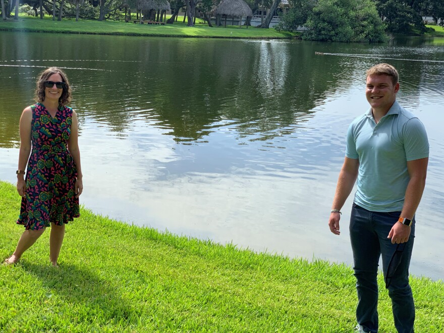 A professor and student stand on a lawn near a pond at Eckerd College in St. Petersburg