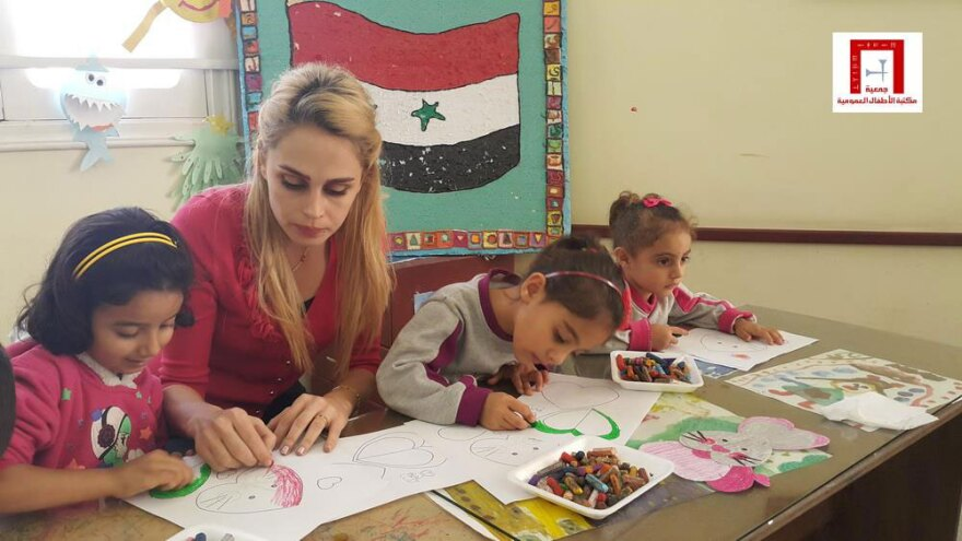 Ahlam Salama with children making art in Syria for the show
