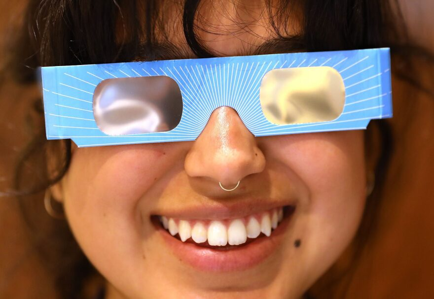 Warby Parker employee Karolyna Landin poses with a pair of solar eclipse glasses that the eyeglass store is giving out for free on Aug. 11, 2017 in New York City. To view the upcoming total solar eclipse on Aug. 21, eye protection is essential. (Spencer Platt/Getty Images)