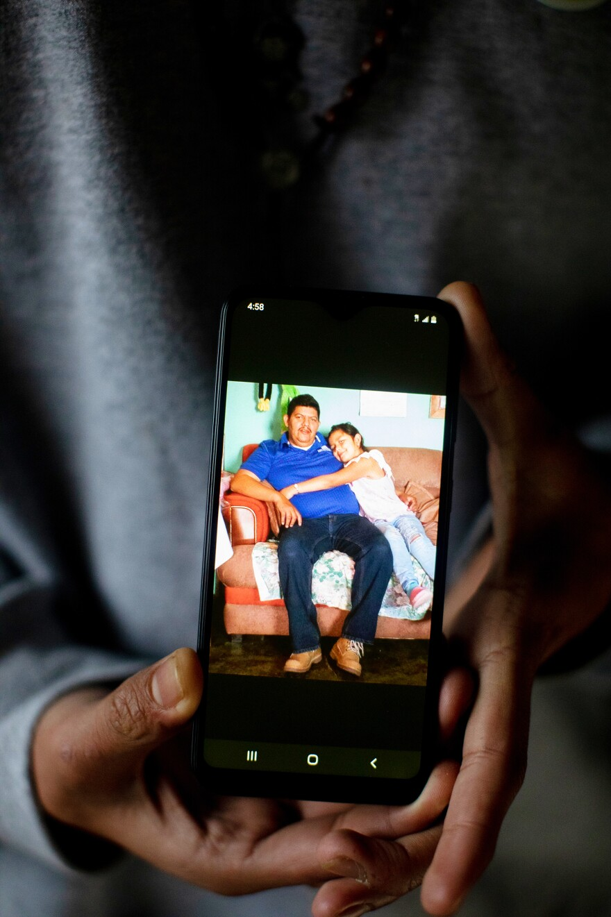 Marvin holds his cell phone with a photograph of his father and younger sister. He currently lives with his sponsor, his uncle, and attends high school while he waits for his immigration court date.