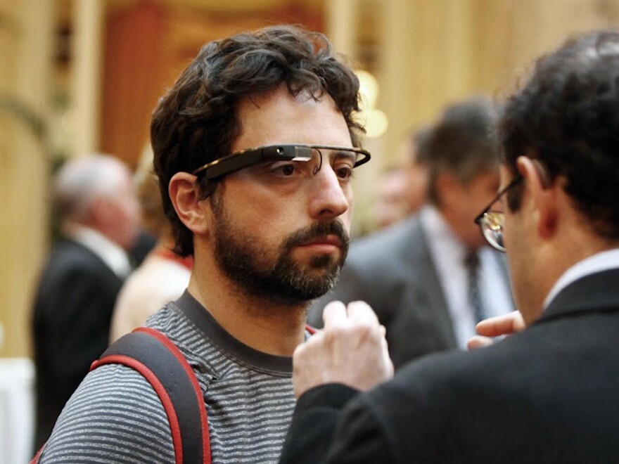 Google co-founder Sergey Brin wears Google's Project Glass prototype publicly for the first time while attending a charity function in San Francisco. Google is suspending public sales of its first generation of Google Glass next week.