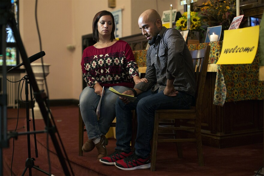 Carly Garcia comforts her husband, Alex, as he nervously reads from a prepared statement during an interview with a TV news station from Poplar Bluff.
