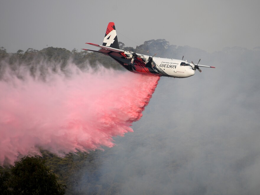 An air tanker operated by Canada-based Coulson Aviation drops fire retardant on the Morton Fire burning in bushland close to homes at Penrose, south of Sydney, earlier this month.