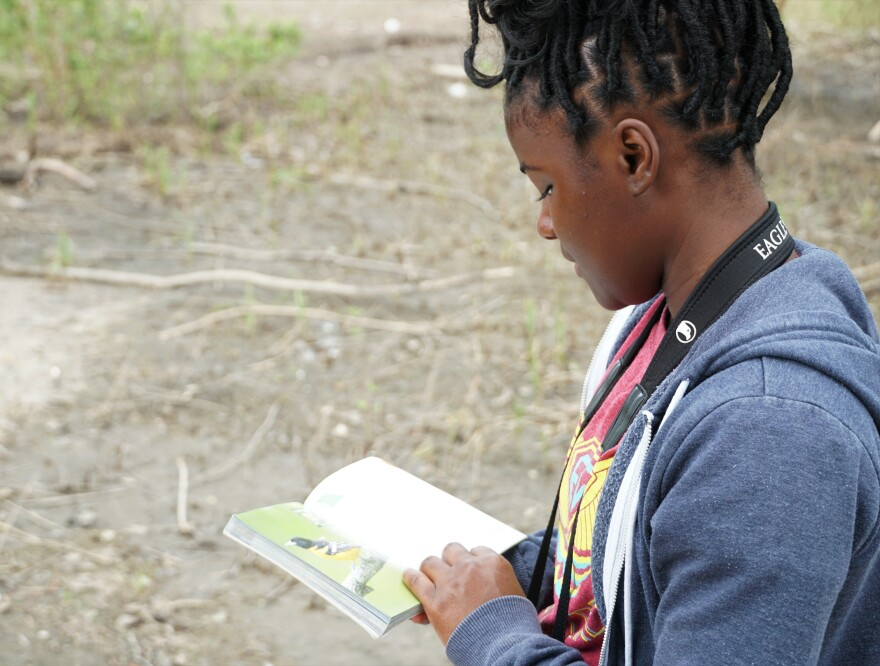 Deija Duncan consults a bird identification guide during a hike at the Audubon Center at Riverlands on July 1, 2019.