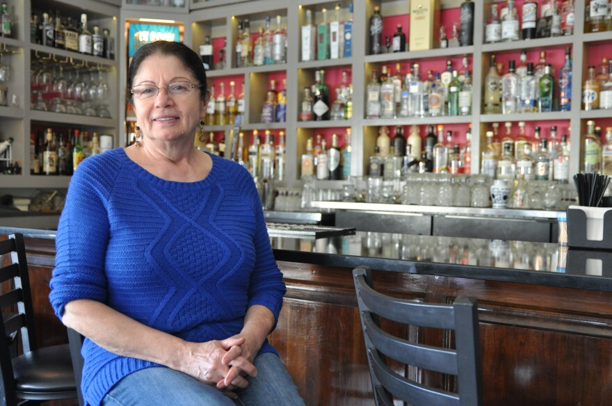 Hamishe Bahrani, at the restaurant she created with her husband: Cafe Natasha's. Bahrami sits in front of a wall of infused gins; her specialty.