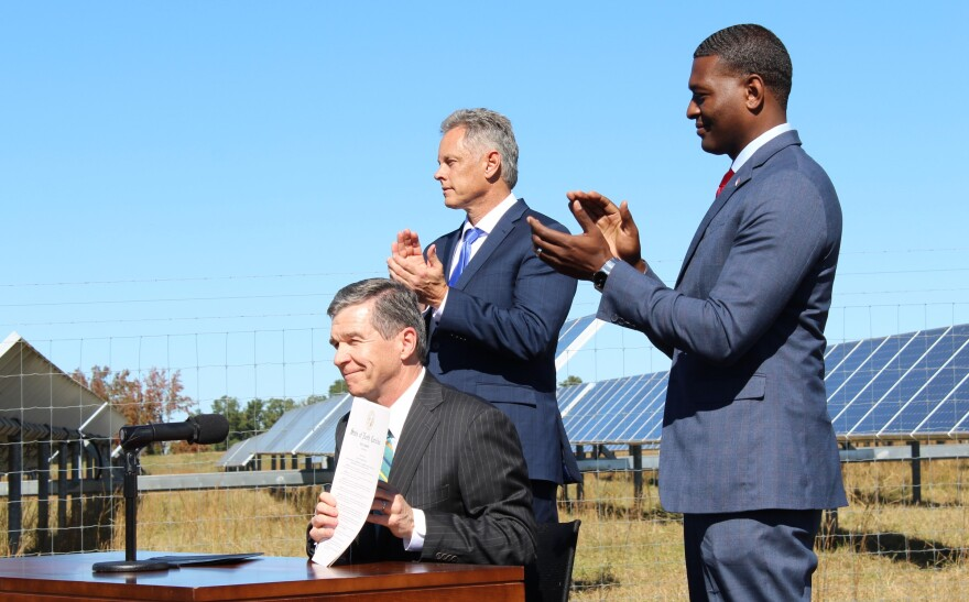 Gov. Roy Cooper (seated) signed Executive Order 80 in 2018 at SAS Institute's solar farm in Cary.  With him were DEQ Secretary Michael Regan (right) and SAS executive Jerry Williams.