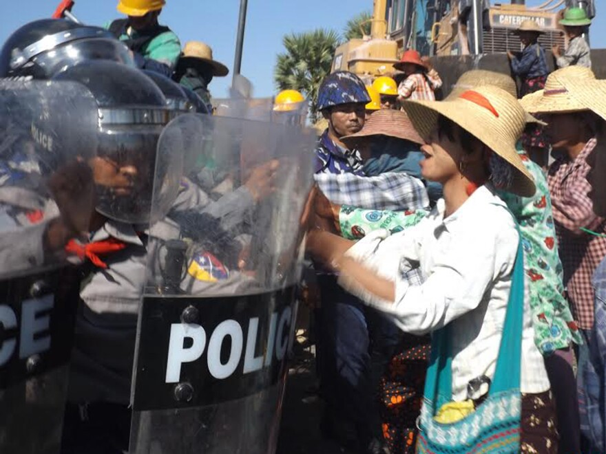 Farmers confront riot police at the site of the Letpadaung copper mine in northwestern Myanmar on Monday. A woman was fatally shot during a crackdown on protesters at the Chinese-backed copper mine.