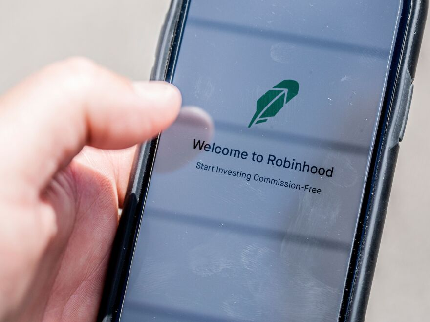 The Robinhood investment app appears on a smartphone in this photo illustration. Day trading has surged during the coronavirus pandemic as stay-at-home people try buying and selling stocks, often for the first time.