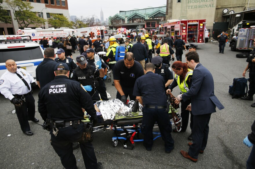 First responders treat injured passengers after a New Jersey Transit train crashed into the platform at Hoboken Terminal during morning rush hour on Thursday.