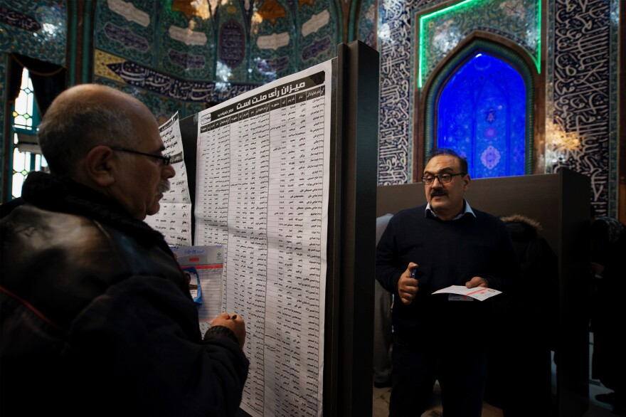 The lists of candidates are placed on a board in the middle of Hoseyniye Ershad, one of the main voting locations in Tehran. More than 7,000 candidates are hoping to win spots in Iran's 290-seat parliament.