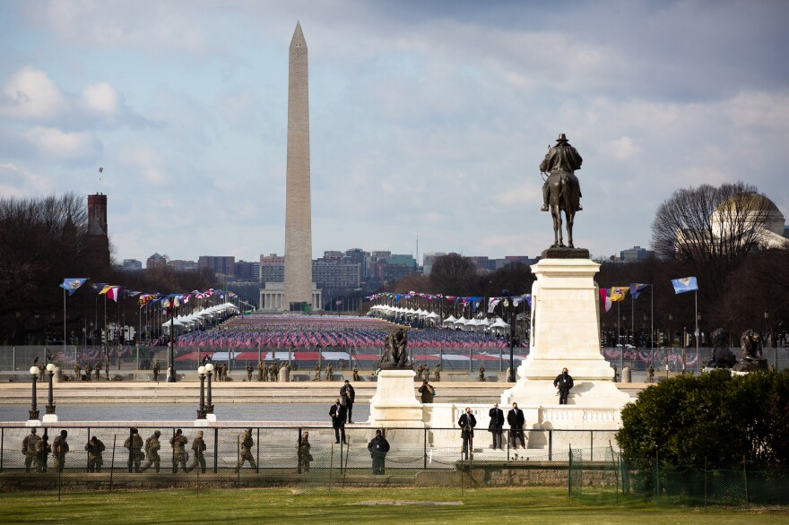 National Guard and security personnel patrol the National Mall, which has a display of nearly 200,000 flags to represent the people who could not attend the inauguration ceremonies because of the pandemic.