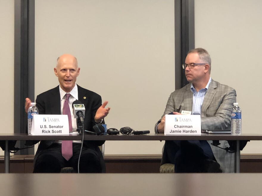 Senator Rick Scott sits at a Tampa at the Greater Tampa Chamber of Commerce along with Chairman Jamie Harden.