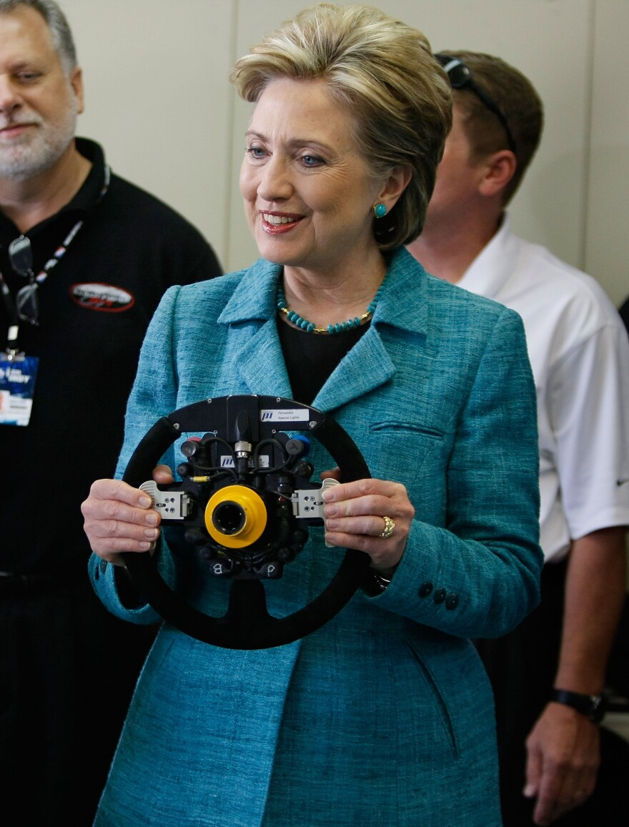 Hillary Clinton holds the steering wheel for the Indy race car of Sarah Fisher in 2008. Clinton says she hasn't gotten behind the wheel herself since 1996.