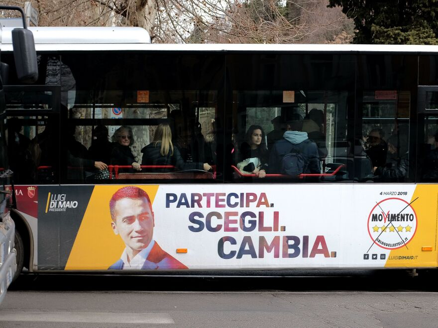 """An election poster for the 5-Star Movement showing leader Luigi di Maio and the motto """"Participate. Choose. Change"""" is seen on the side of a bus in Rome ahead of the March 4 general elections."""