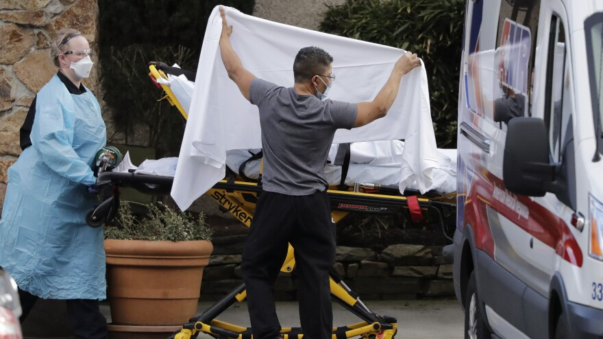 A staff member holds a sheet as a privacy screen as a person on a stretcher is taken to an ambulance from Life Care, a Kirkland, Wash., nursing facility where dozens of people are being tested for the COVID-19 virus.