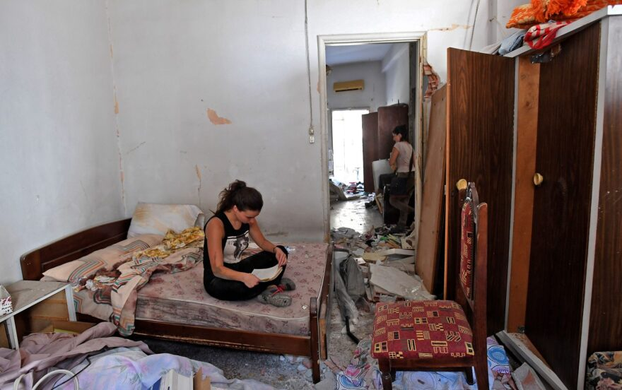 A woman cleans the rubble in her damaged house. two days after a massive explosion shook the Lebanese capital of Beirut.