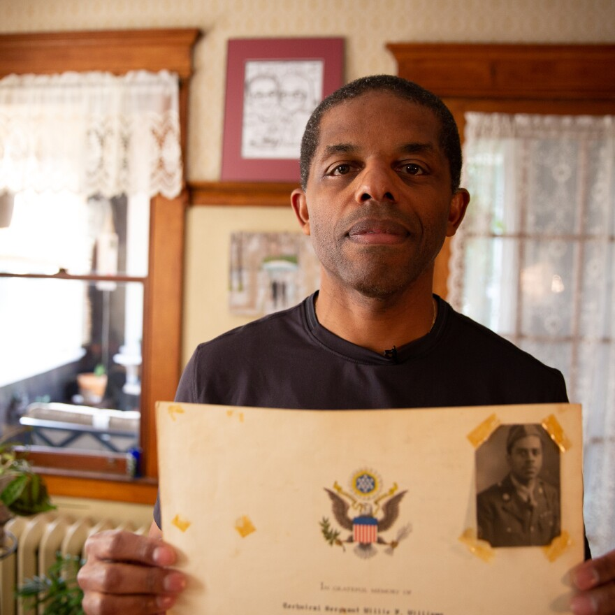 David McGhee holds up an award given to his grandfather, Sgt. Willie F. Williams, for his military service in World War II.
