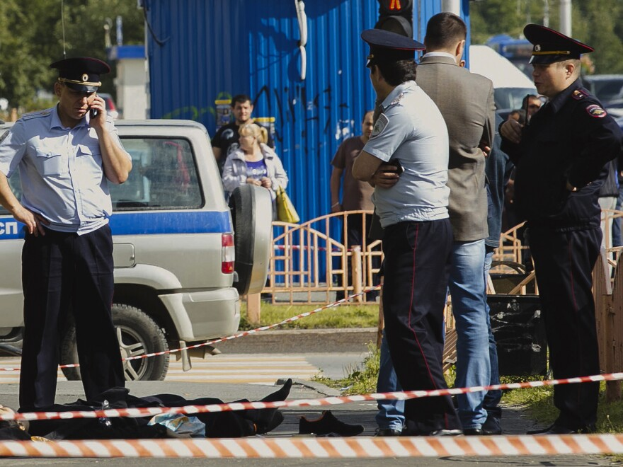 Police officers stand over the body of a man killed after he allegedly carried out a stabbing attack on Saturday in the Siberian city of Surgut, Russia.