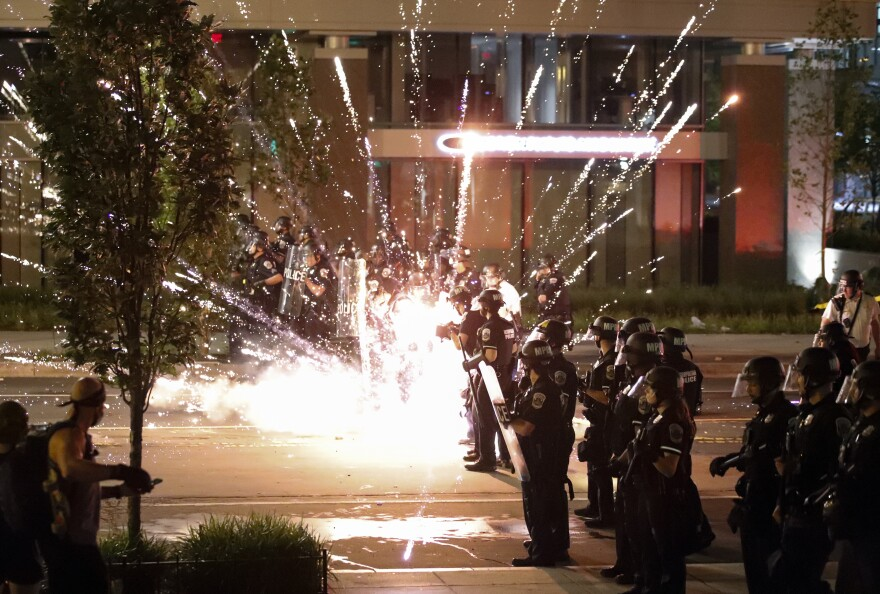 A firework explodes by a police line as demonstrators gather to protest the death of George Floyd, Saturday, May 30, 2020, near the White House in Washington.