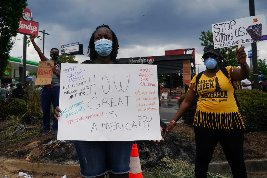 People hold signs toward traffic outside a burned Wendys restaurant on the second day following the police shooting death of Rayshard Brooks in the restaurant parking lot June 14, 2020, in Atlanta, Georgia. (ELIJAH NOUVELAGE/AFP via Getty Images)