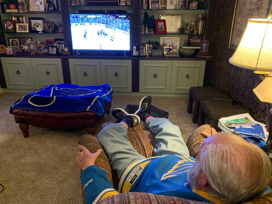 Longtime Blues' fan John Oefelein in his game watching position at home. In his recliner with his feet elevated while viewing Game 2 of the Stanley Cup Final in a Blues' jersey.