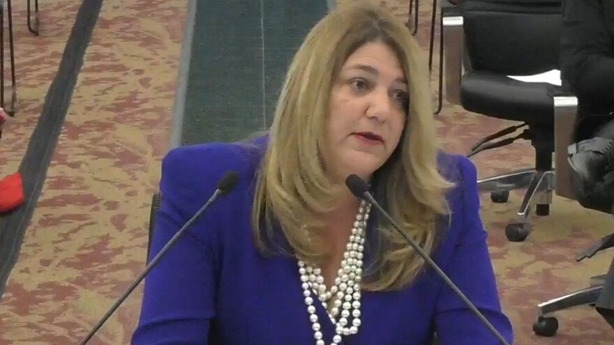 Woman sits at table in purple suit with pearls in front of microphones