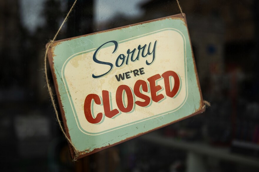 """A sign that hangs on a door reads """"sorry, we're closed"""""""