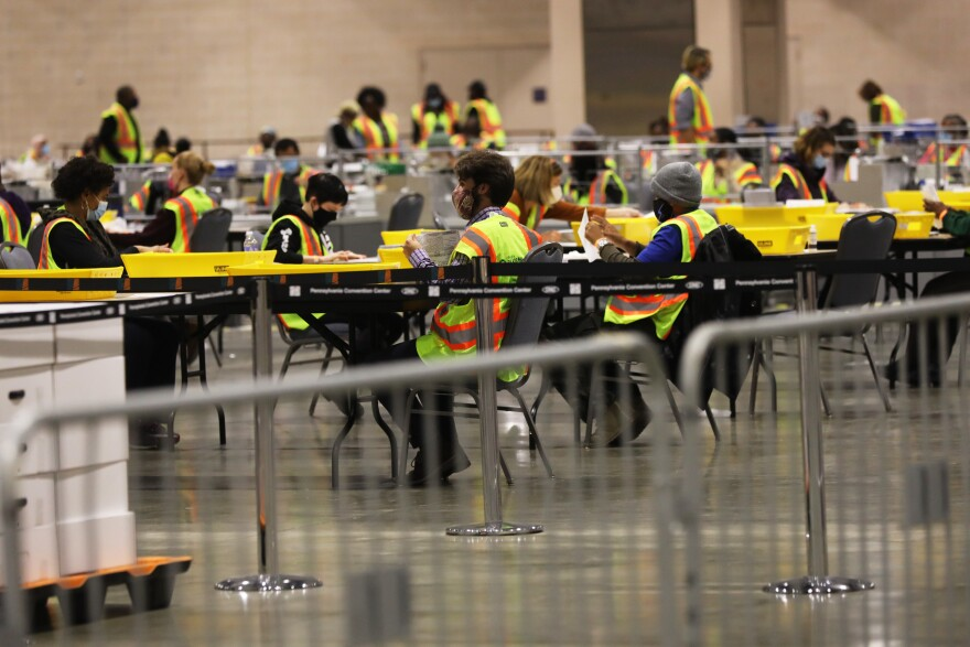 Election workers count ballots on November 3 in Philadelphia. While the election was logistically complicated and there were efforts by foreign and domestic actors to disrupt the election, it appears a record number of Americans cast ballots.