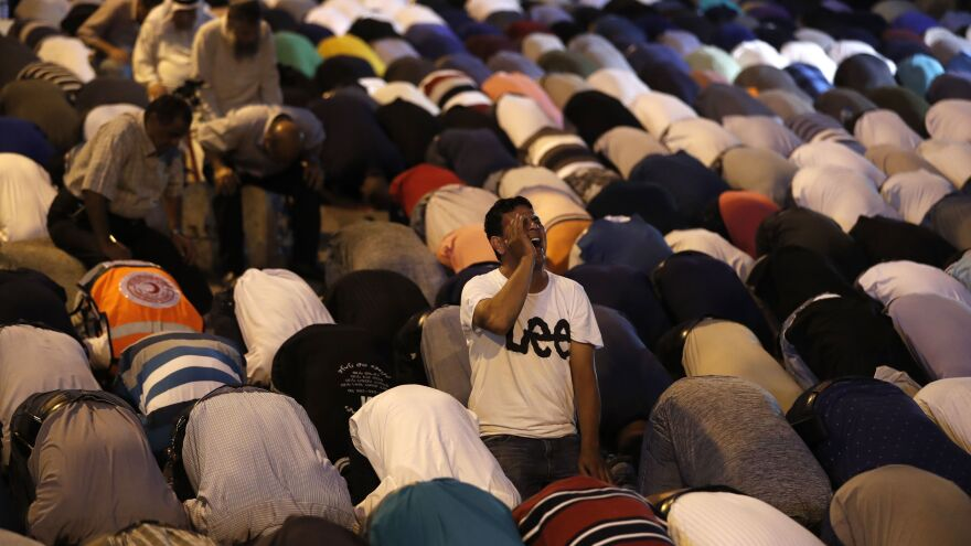Palestinian Muslim worshippers pray outside an entrance to the Al-Aqsa mosque compound in Jerusalem's Old City on Sunday. They gathered to protest new Israeli security measures implemented at the holy site following an attack that killed two Israeli policemen the previous week.