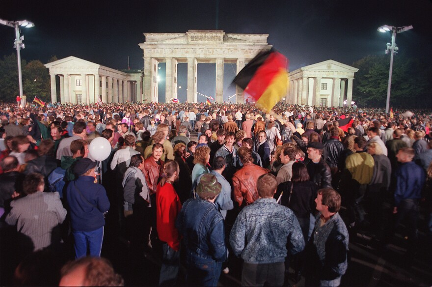 "German youths wave flags as they celebrate the country's reunification at the Brandenburg Gate in Berlin in 1990. One Russian lawmaker recently referred to West Germany's ""annexation"" of East Germany and said it was less legitimate than Russia's ""reunification"" with Crimea."